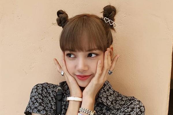 Bên cạnh phong cách ngầu, cá tính thường thấy, Lisa của Black Pink cũng rất đáng yêu với kiểu tóc búi hai bên. Cô nàng còn gắn thêm một chiếc kẹp trái tim cho thêm phần điệu đà.