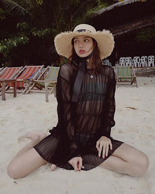 Lisa đang có chuyến đi nghỉ dưỡng ở biển Phuket tại quê nhà Thái Lan. Cô nàng lần đầu tung ảnh diện bikini khoe vóc dáng. Em út Black Pink chọn bộ đồ tắm hai mảnh kiểu thể thao, tông màu xanh nổi bật. Bên ngoài, Lisa mặc thêm một chiếc váy ren đen siêu mỏng, tạo cảm giác nửa kín nửa hở.
