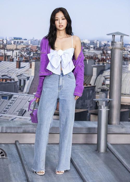 Crotop thắt nơ của nhà mốt Chanel được Jennie phối với cardigan tím cùng jeans ống rộng và túi xách xuyệt tông, set đồ giúp cô nàng khoe vẻ tươi tắn tuy nhiên khí chất của Jennie còn nhạt nhòa.