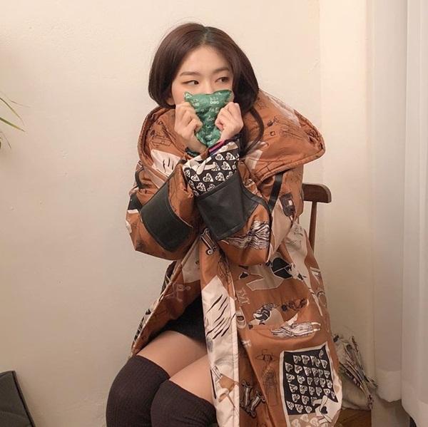 Seul Gi mặc áo khoác, cầm túi giữ nhiệt cho ấm khi diện váy ngắn.