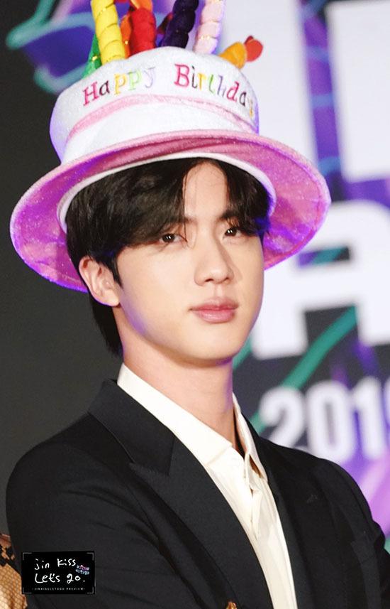 Ngày 4/12 cũng là sinh nhật của Jin và anh chàng được các thành viên tặng chiếc mũ chúc mừng hài hước ngay trên thảm đỏ.