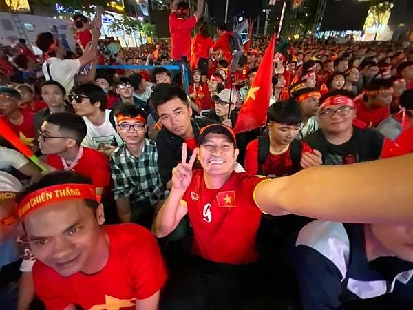 Huy Khánh mặc áo thi đấu của đội tuyển Việt Nam và hòa vào dòng người đi cổ vũ bóng đá. Anh cho biết bản thấy thấy vui, cảm động khi đội tuyển bóng đá nam và nữ của Việt Nam đã vô địch SEA Games 30.