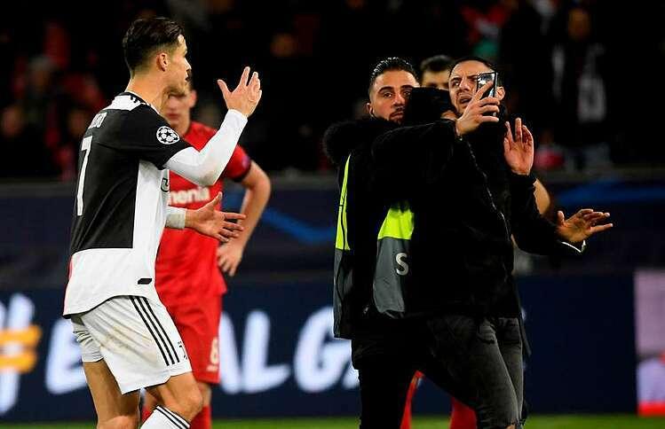 Ronaldo phản ứng với CĐV túm cổ đòi chụp ảnh chung. Ảnh: Givemesport.