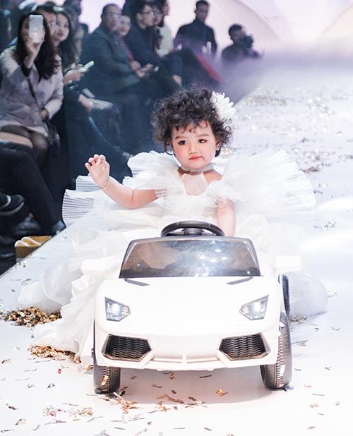 Nguyễn Ngọc An Nhiên lên sân khấu với chiếc ô tô điện màu trắng. Cô nhóc diện váy xòe như búp bê, vừa đi giữa sàn runway vừa vẫy tay chào khán giả. Mới 2 tuổi và làm quen thời trang được vài tháng nhưng An Nhiên đã tỏ ra rất thông minh, lanh lợi, yêu thích ánh đèn sân khấu.