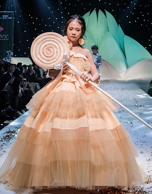 Các người mẫu nhí xuất hiện lộng lẫy trên sàn diễn với đạo cụ đặc biệt là những chiếc kẹo mút siêu to khổng lồ.