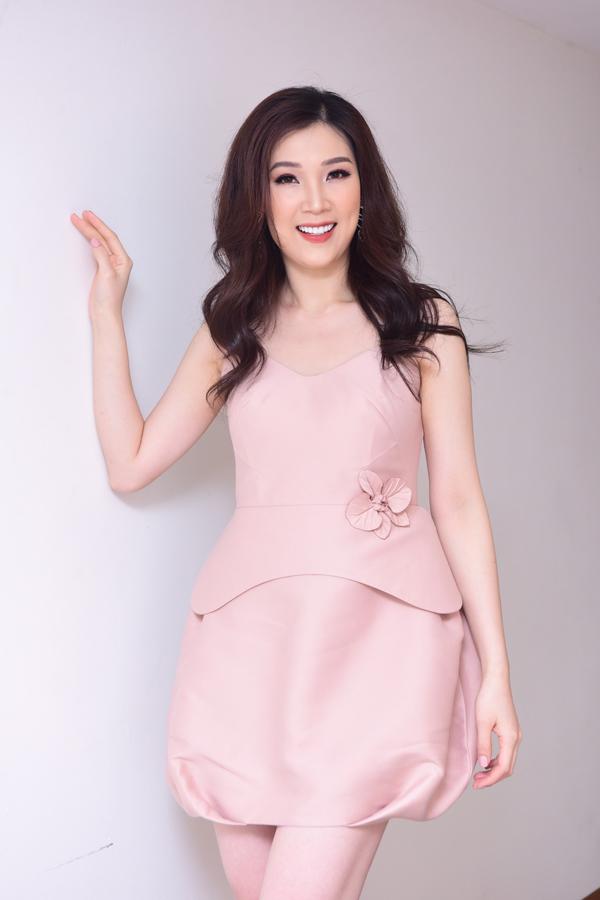 Hoa hậu Phí Thùy Linh xuất hiện từ sớm tại trường Đai học Kinh tế Quốc dân. Người đẹp diện đầm hai dây màu hồng pastel với điểm nhấn bông hoa lệch bên eo.