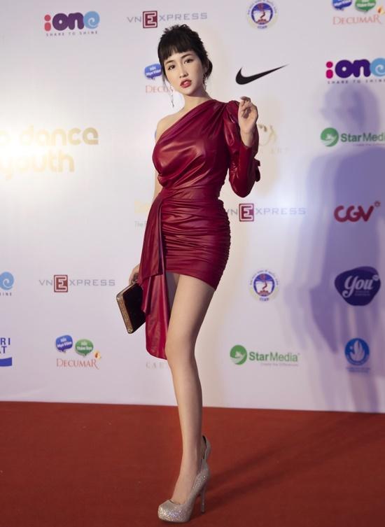 Nữ DJ sinh năm 1993 diện đầm ngắn khoe chân thon. Thiết kế lệch vai, tà váy bất đối xứng giúp Trang Moon tạo điểm nhấn. Cô phối đồ với clutch và giày cao gót lấp lánh, sang trọng.