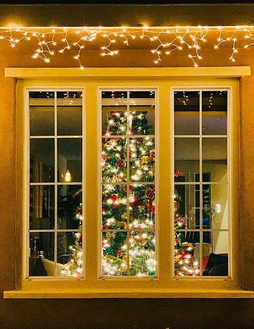 Anh đặt cây thông nhiều màu sắc ở cửa sổ phòng khách.