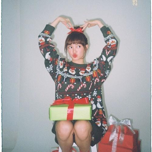 Kaity Nguyễn mặc trang phục họa tiếtông già Noel đáng yêu bên hộp quà. Cô không ra đường đêm Noel.