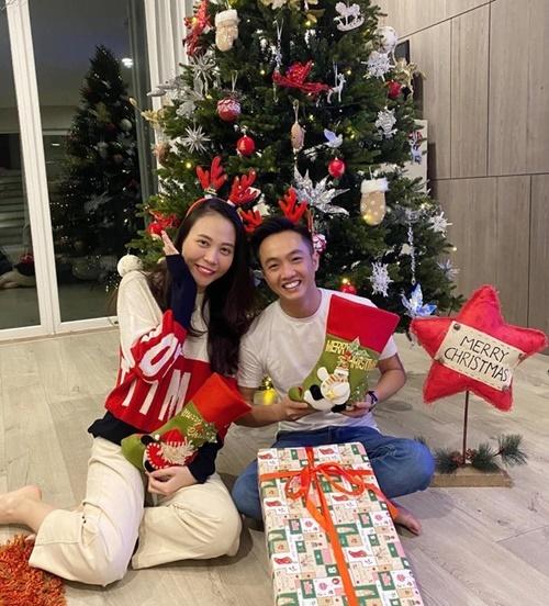 Cường Đô La và Đàm Thu Trang đeo phụ kiện sừng tuần lộc, ôm gói quà, tạo dáng bên cây thông Noel. Cặp đôi gắn bó như hình với bóng sau khi kết hôn.
