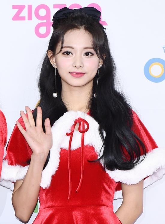 Nữ idol sinh năm 1999 diện bộ đầm Santa đáng yêu và nổi bật. Màu tóc đen và son đỏ tôn thêmvẻ đẹp kiều diễm mặn màcủa Tzuyu.