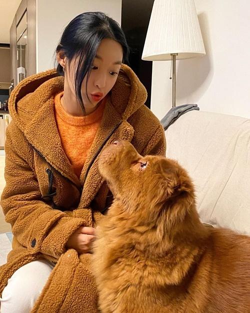 Seol Hyun mặc áo khoác bông tông xuyệt tông với màu lông của cún cưng.