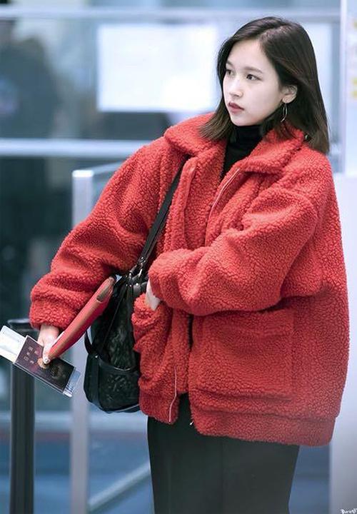 Áo khoác vải bông xù là kiểu đồ lên ngôi trong Kbiz mùa đông năm nay. Món đồ này còn được gọi là áo khoác Teddy nhờ biến người mặc thành tròn trĩnh, đáng yêu như một chú gấu bông. Mina nổi bật ở sân bay khi diện áo bông màu đỏ rực.