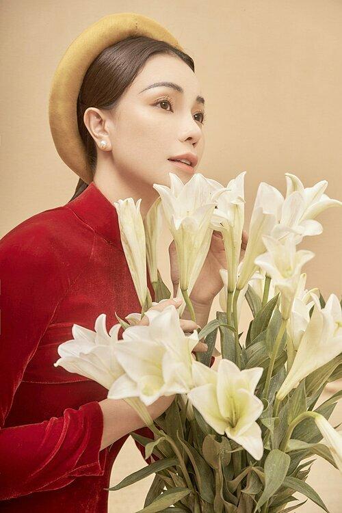 Trà Ngọc Hằng diện áo dài nhung đỏ, đầu đội mấn. Với cô, áo dài mang ý nghĩa đặc biệt khi tôn lên hồn cốt Việt Nam và tạo nét duyên cho người mặc.