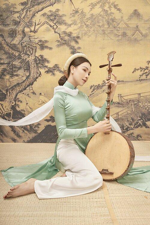 Trà Ngọc Hằng mặc áo dài truyền thống nền nã trong bộ ảnh chào xuân. Cô sử dụng đàn nguyệt, sáo, ấm trà làm đạo cụ,tạo nên bối cảnh đậm chất Á Đông cho những bức hình.