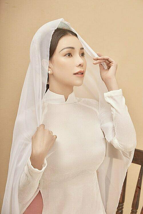 Cô dùng khăn voan trắng làm phụ kiện khi mặc mẫu áo dài trắng truyền thống.