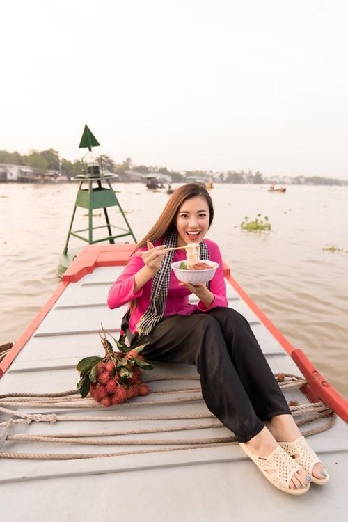 Ngồi trên ghe, Kim Duyên thưởng thức món hủ tiếu.