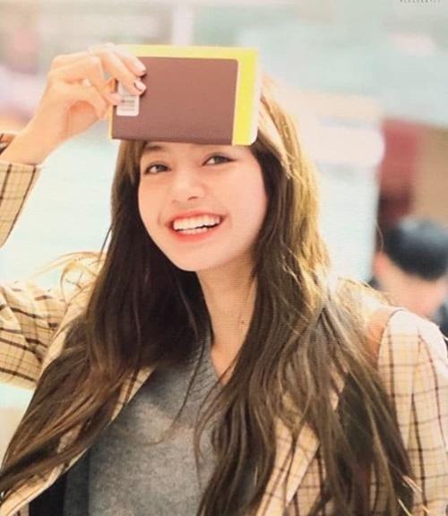 Lisa xấu hổ che mái khi bắt gặp ống kính của fan. Người hâm mộ trêu chọc cô nàng dường như hết keo xịt tóc, phải đổi style mái khi ra sân bay.