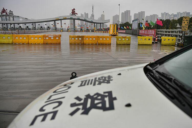 Một chiếc xe cảnh sát đỗ tại con đường bị phong tỏa nhằm ngăn chặn người dân rời khỏi Vũ Hán, tỉnh Hồ Bắc. Ảnh: AFP.