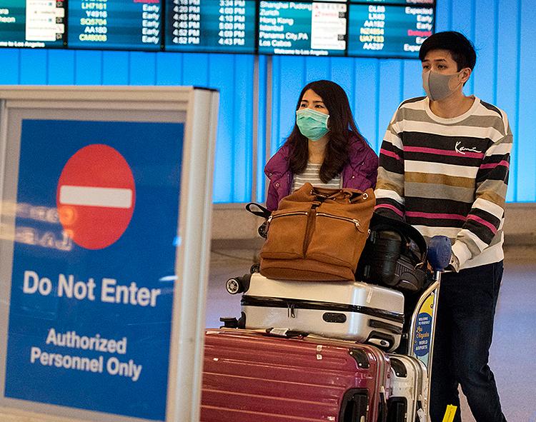 Hành khách đeo khẩu trang bảo vệ giữa dịch coronavirus lây lan ở Sân bay Quốc tế Los Angeles. Ảnh: AFP.