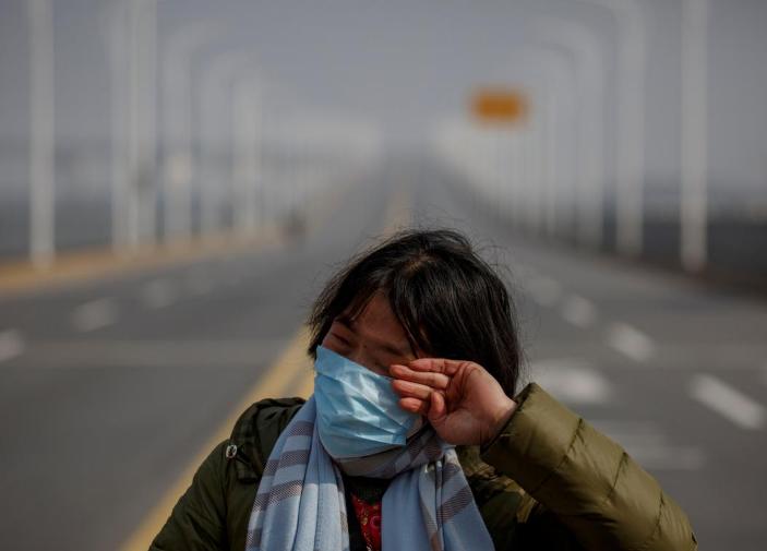 Người mẹ Trung Quốc gạt nước mắt cầu xin cho con gái ung thư vượt qua trạm kiểm soát để đến bệnh viện. Ảnh: Reuters.