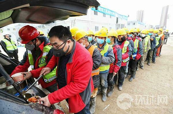 Hàng dài công nhân xếp hàng để đợi lấy đồ ăn.
