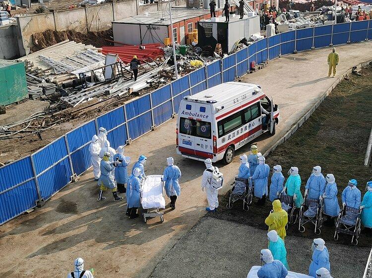 Nhân viên y tế đứng đợi xe cứu thương chở bệnh nhân vào viện dã chiến. Ảnh: Global Times.