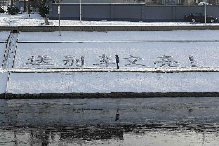 Một người đàn ông vẽ trên tuyết dòng chữ Vĩnh biệt Li Wenliang tại Bắc Kinh. Ảnh: AP.