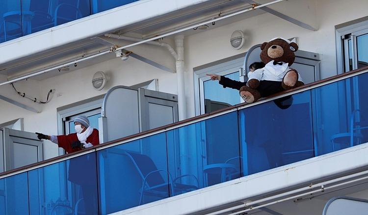 Hành khách nói chuyện với nhau trên ban công cabin của họ trên tàu du lịch Diamond Princess. Ảnh: Reuters