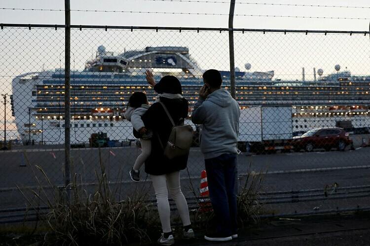Các thành viên gia đình của hành khách trên du thuyền Diamond Princess vẫy tay và nói chuyện với họ qua điện thoại. Ảnh: Reuters.