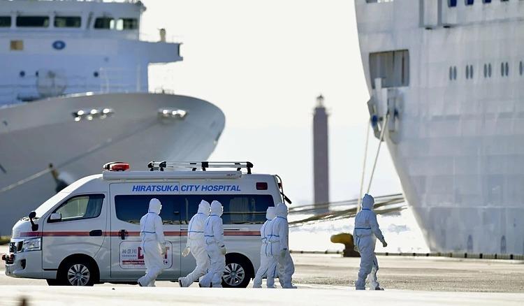 Các nhân viên y tế trong bộ đồ bảo hộ đi bộ về phía tàu du lịch Diamond Princess cập cảng ở Yokohama hôm 11/2. Ảnh: Kyodo.