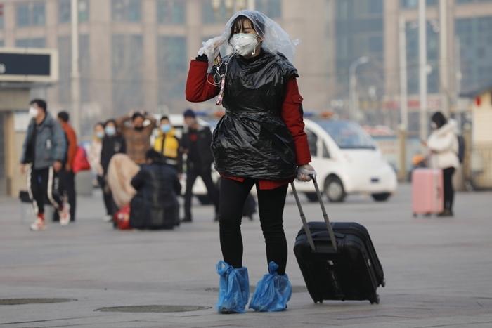 Một hành khách tại nhà gaBắc Kinh che đầu và cơ thểbằng túi nilon để phòng ngừa virus corona. Ảnh: EPA-EFE.