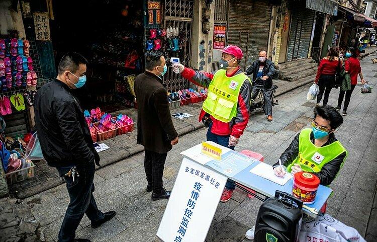 Nhân viên y tế kiểm tra thân nhiệt người đi bộ ở Quảng Châu, Trung Quốc. Ảnh: EPA.