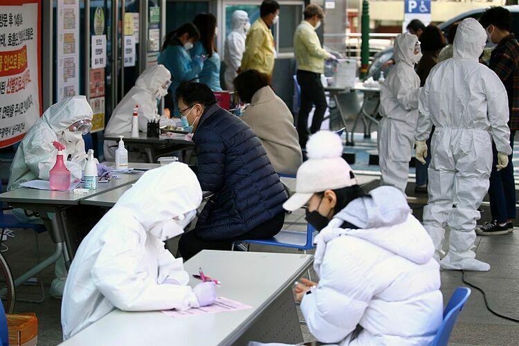 Những người bị nghi ngờ bị nhiễm nCoV trao đổi với nhân viên y tế về việc xét nghiệm tại Daegu, ngày 21/2.