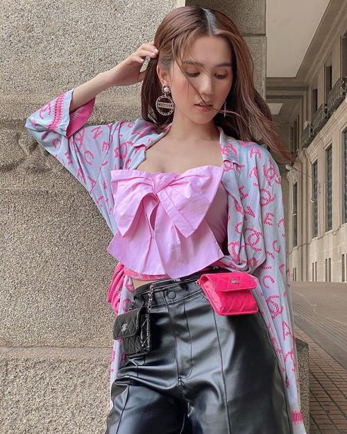 Trong bộ cánh xuống phố mới đây, Ngọc Trinh diện cả cây đồ Chanel, phối hai tông màu đen và hồng đang hot. Người đẹp mix chiếc áo hai dây đính nơ hot hit với áo choàng và set túi mini, tạo hình ảnh phóng khoáng.