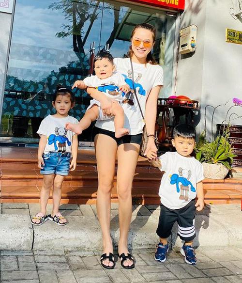 Hải Băng khoe chân thon khi đưa ba con ra trước cửa tắm nắng.