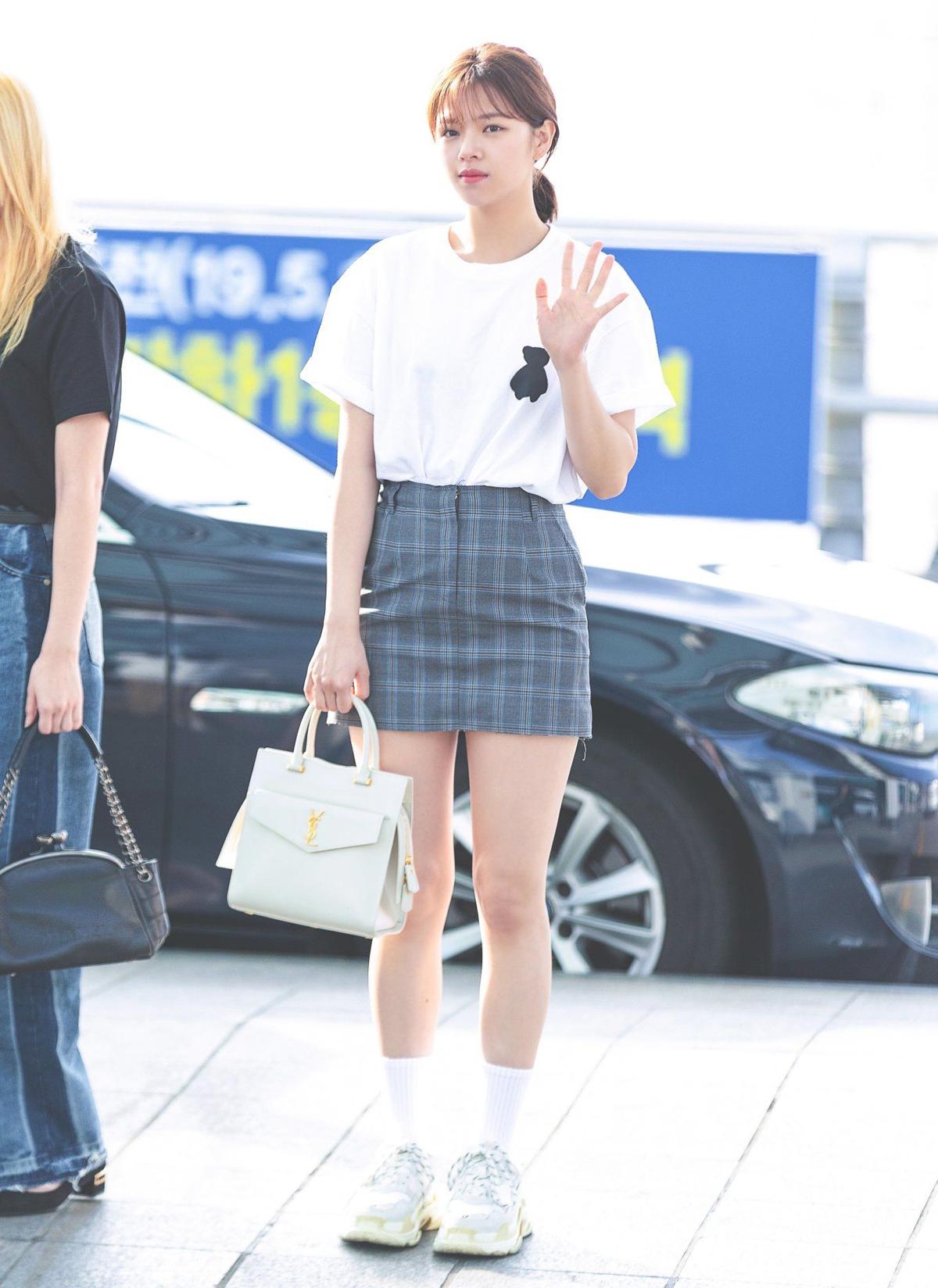 Jeong Yeon nữ tính với áo thun trắng phối cùng váy kẻ sọc, và giày chunky của thương hiệu Balenciaga. Set đồ đơn giản này của Jeong Yeon trở nên nổi bật khi cô nàng xách túi da Saint Laurent có giá gần 2500 đô.