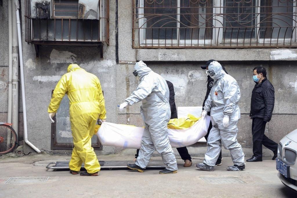 Nhân viên nhà tang lễ di chuyển thi thể một người nghi ngờ nhiễm nCoV từ một khu chung cư Vũ Hán hồi đầu tháng 2. Ảnh:AP.