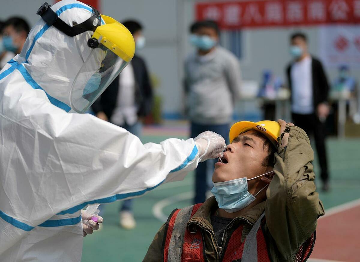 Nhân viên y tế lấy mẫu thử từ họng của công nhân xây dựng để kiểm tra axit nucleic tại Vũ Hán ngày 7/4. Ảnh: Reuters.