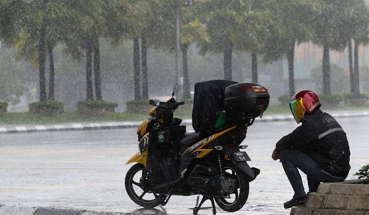 Một người lái xe giao thức ăn trú ẩn dưới một cây cầu ở Malaysia giữa trời mưa ngày 6/4. Ảnh: AFP.
