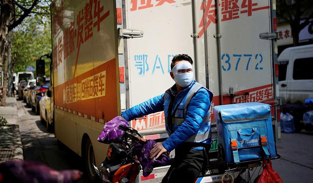 Một nhân viên giao hàng đeo mặt nạ che chắn ở khu dân cư ở Vũ Hán hôm 13/4. Ảnh: Reuters.
