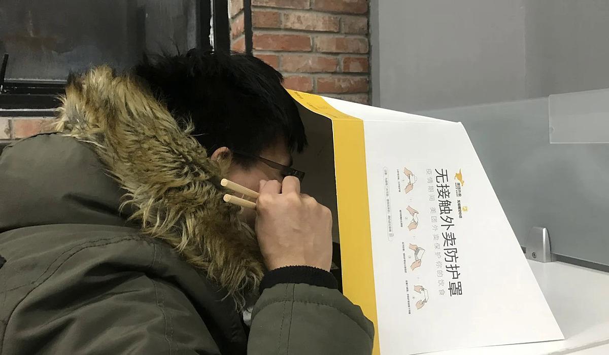 Một người ăn đồ ăn được che chắn bởi vỏ hộp nhằm tránh tiếp xúc từ Meituan. Ảnh: SCMP.