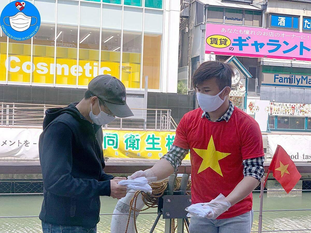 Một thành viên trong nhóm tặng khẩu trang cho người dân.