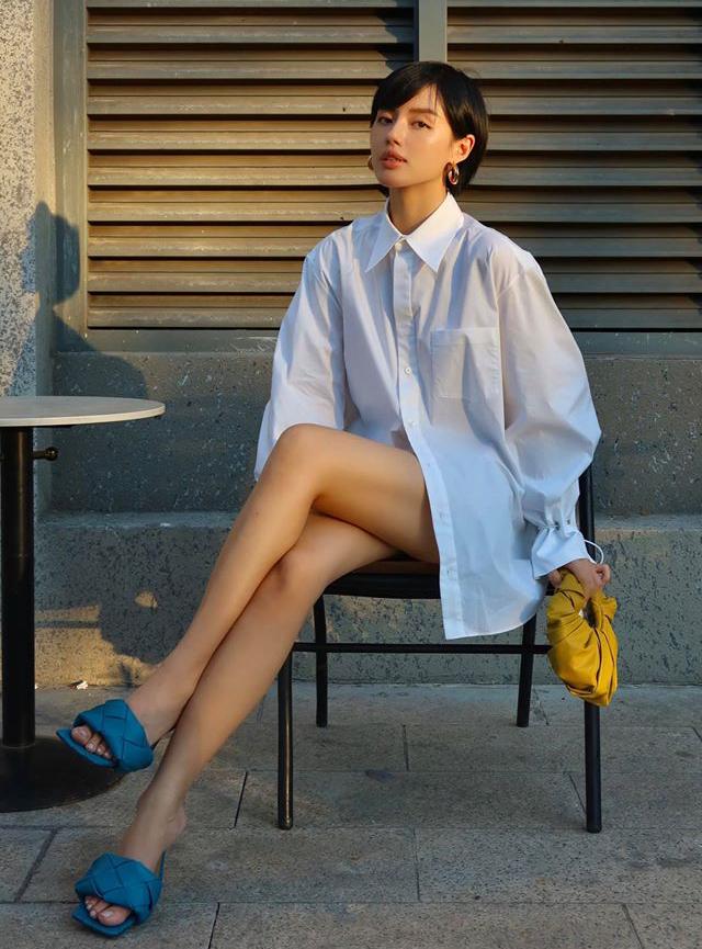 Chiếc sơ mi trắng oversized đậm chất mượn của bố được Khánh Linh kết hợp cùng phụ kiện Bottega Veneta để tạo nên cây đồ đẳng cấp dạo phố.