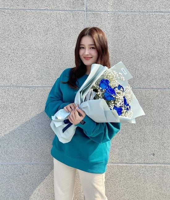 Nancy ôm bó hoa xanh tông xuyệt tông với áo.