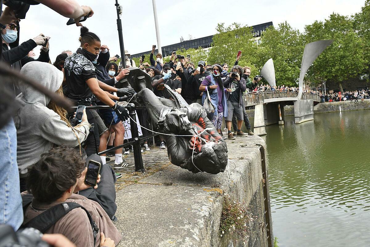 Bức tượng bị người dân buộc dây thừng đẩy xuống hồ. Ảnh: AP.