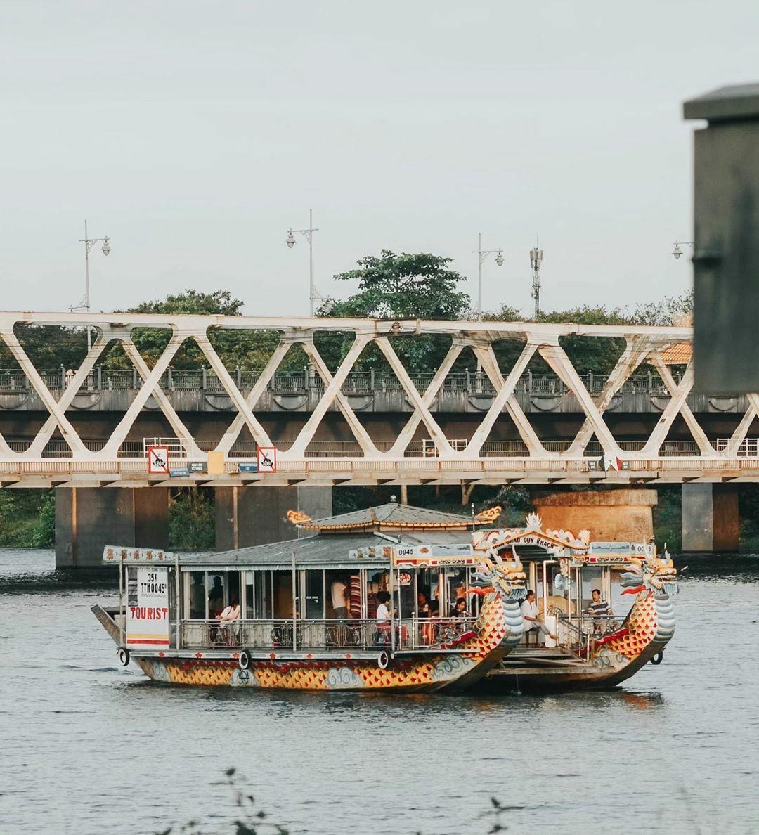 Nhiều du khách thích ngồithuyền rồng nghe ca Huế trên sông Hương. Phía sau là cầu đường sắt Bạch hổ và cầu Dã Viên.
