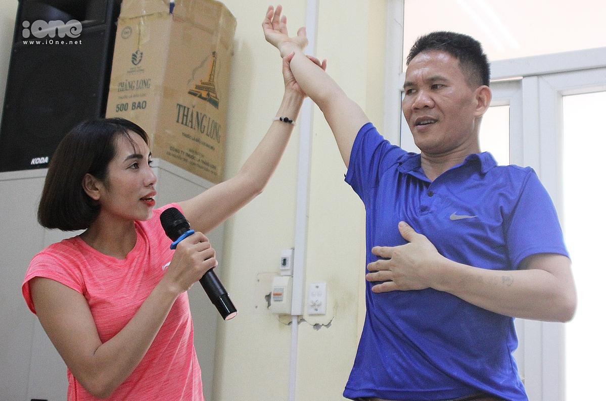 Cô giáo Nhung cầm tay chỉ động tác cho các học viên trong lớp.