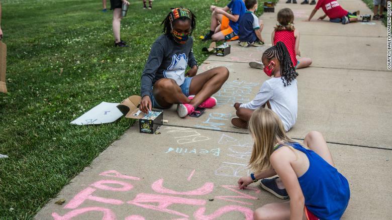 Trẻ em dùng phấn vẽ trên vỉa hè các khẩu hiệu Black lives matter.