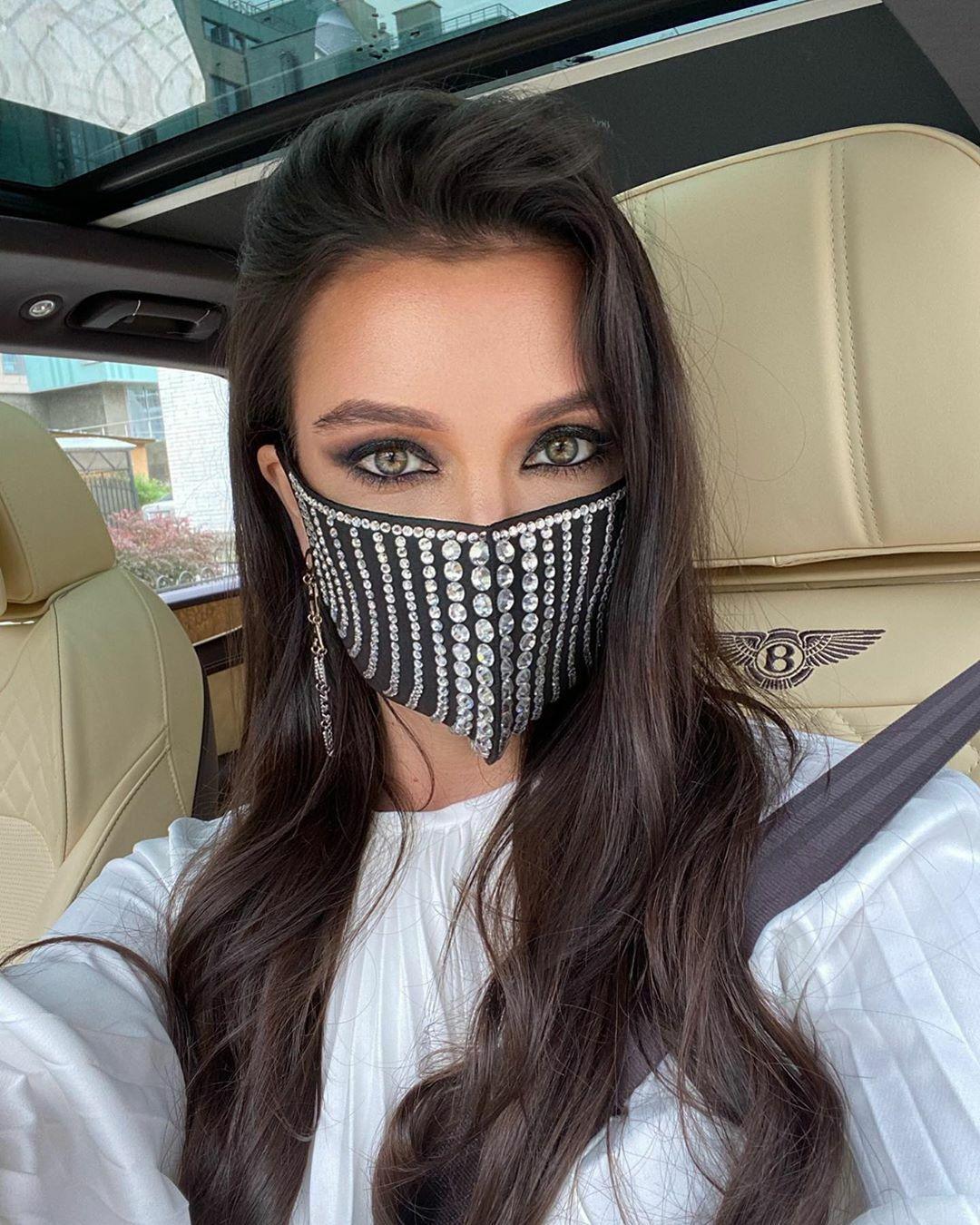 Hội con nhà giàu khắp nơi trên thế giới pose hình từ đi hàng ngàn dặm trong những chiếc siêu xe cho đến nằm phơi nắng ở các khách sạn năm sao. Trong ảnh, nhà thiết kế người Nga Dimavika tạo dáng trước một chuyến đi trên xe Bentley. Cô đeo khẩu trang thiết kế riêng đính đầy kim cương.